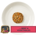 Isolated aerial image of Encore beef dog food pate with vegetables on a plate